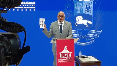 Venezuelan National Assembly President Jorge Rodríguez holds up document during a press conference.